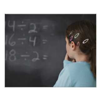 Girl looking at math equations on blackboard posters