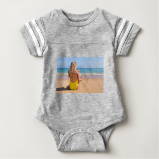 Girl on beach smearing sunscreen on skin.JPG Baby Bodysuit