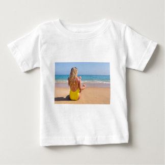 Girl on beach smearing sunscreen on skin.JPG Baby T-Shirt