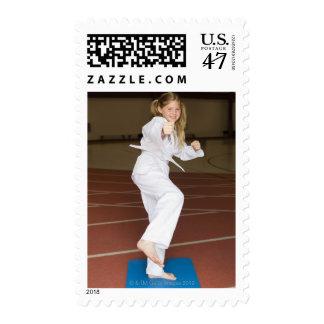 Girl practicing karate postage stamp
