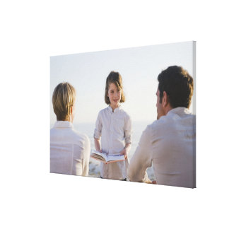 Girl reading a book in front of her parents canvas print