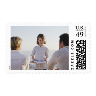 Girl reading a book in front of her parents stamp