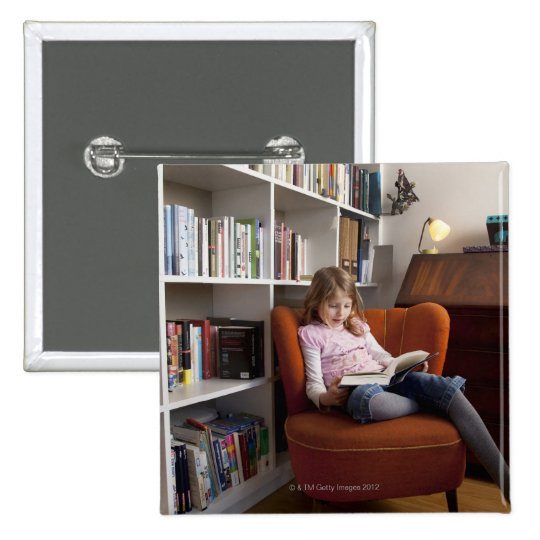 Girl reading by the bookshelf button