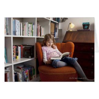 Girl reading by the bookshelf card