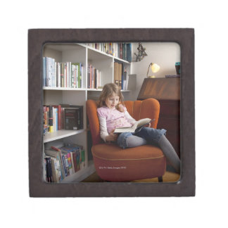 Girl reading by the bookshelf jewelry box