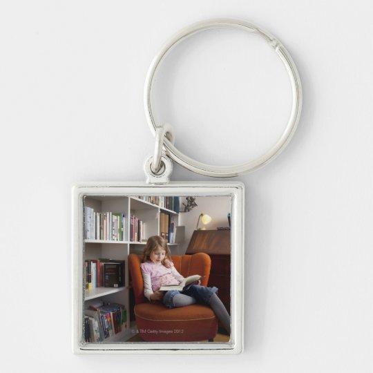 Girl reading by the bookshelf keychain