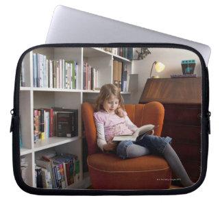 Girl reading by the bookshelf laptop sleeves
