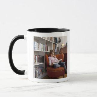 Girl reading by the bookshelf mug