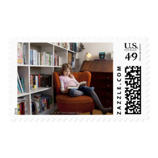 Girl reading by the bookshelf postage stamp