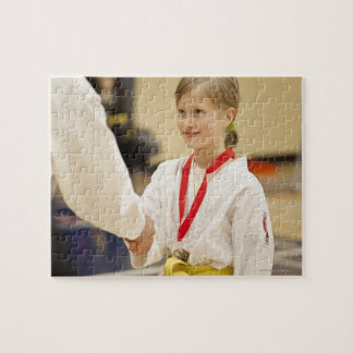 Girl receiving a medal at a Karate championship Puzzles