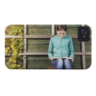 Girl sitting and reading book near vine iPhone 4 case