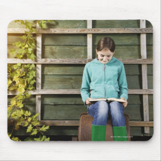 Girl sitting and reading book near vine mouse pad