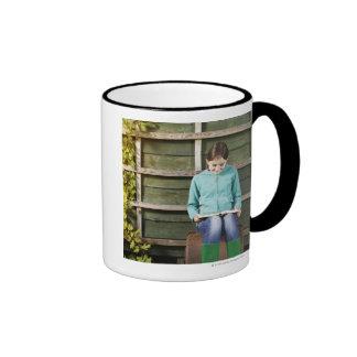 Girl sitting and reading book near vine ringer coffee mug