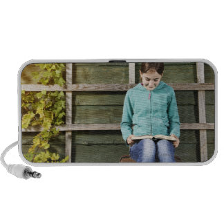 Girl sitting and reading book near vine iPod speakers