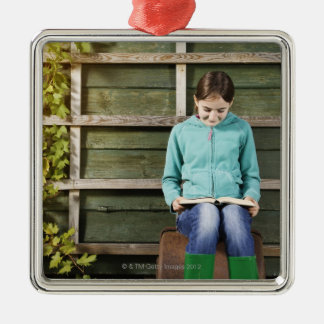 Girl sitting and reading book near vine square metal christmas ornament