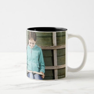 Girl sitting and reading book near vine Two-Tone coffee mug