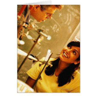 Girl smiling at teacher in chemistry lab card