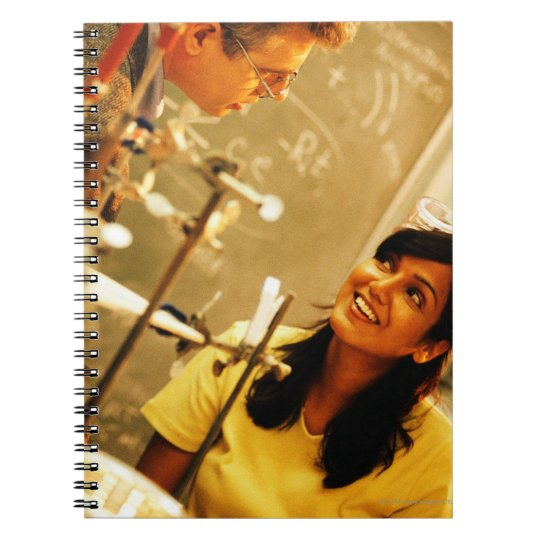 Girl smiling at teacher in chemistry lab notebook