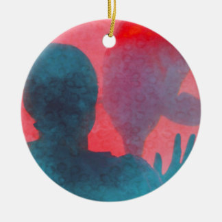 Girl with hand up by dolphin blue pink colored christmas tree ornament