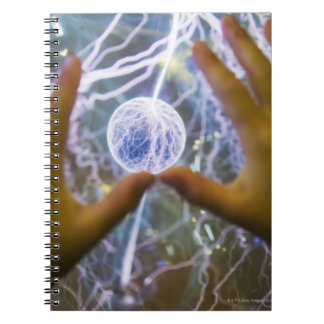 Girls hands on a plasma ball note books