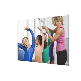 Girls stretching in gymnastics class canvas print