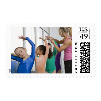 Girls stretching in gymnastics class stamp