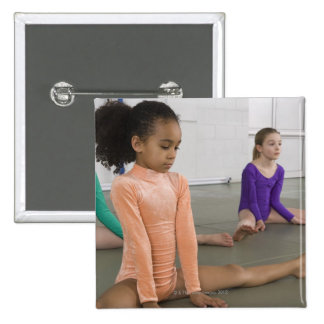 Girls stretching in gymnastics practice buttons