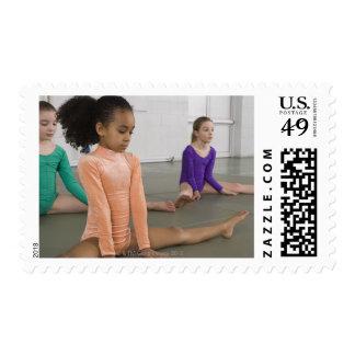 Girls stretching in gymnastics practice postage stamp