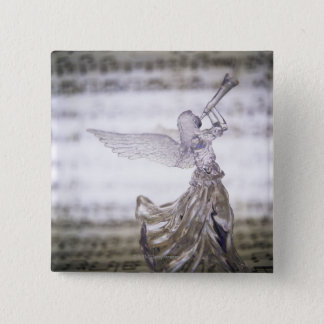 Glass angel playing trumpet and image of sheet button