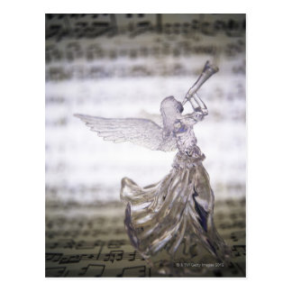 Glass angel playing trumpet and image of sheet postcard