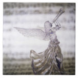 Glass angel playing trumpet and image of sheet ceramic tiles