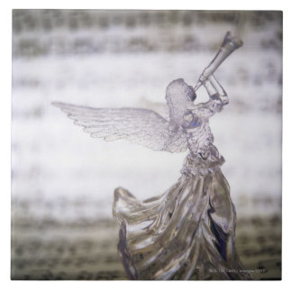 Glass angel playing trumpet and image of sheet tile