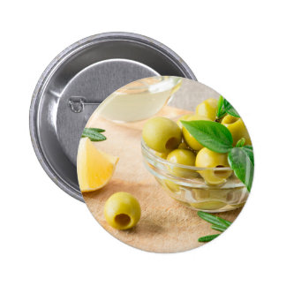 Glass cup with green pitted olives button