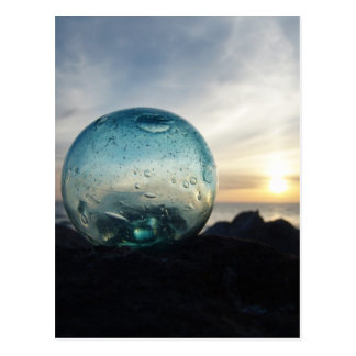 Glass float and sunset postcard