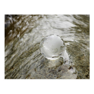 Glass globe on the water stream postcard