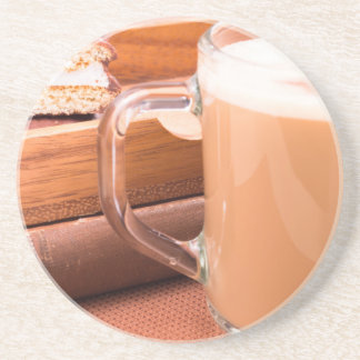 Glass mug with hot chocolate and biscuits drink coaster