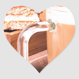 Glass mug with hot chocolate on a table heart sticker