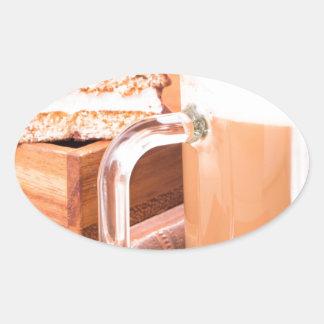 Glass mug with hot chocolate on a table oval sticker
