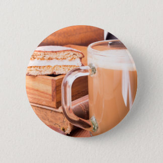 Glass mug with hot chocolate on a table pinback button