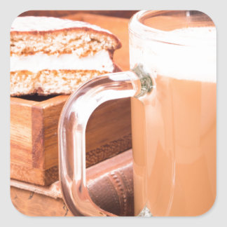 Glass mug with hot chocolate on a table square sticker