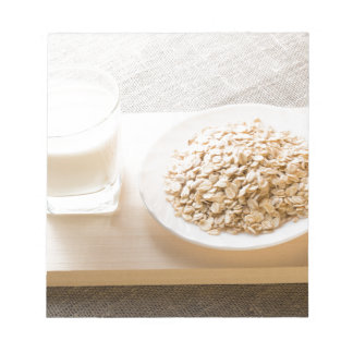 Glass of milk and a plate of cereal closeup notepad