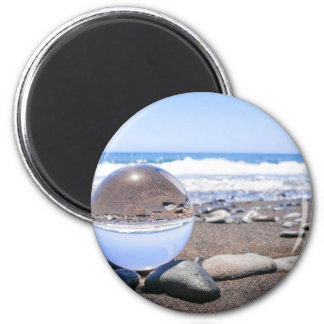 Glass sphere on stones at beach and coast magnet