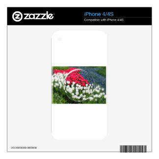 Glass sphere reflecting red white tulips and blue decal for iPhone 4