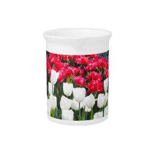 Glass sphere reflecting red white tulips and blue drink pitcher