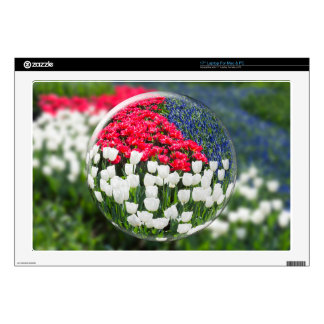 Glass sphere reflecting red white tulips and blue laptop decals