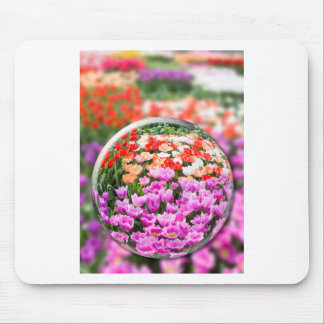 Glass sphere with various tulips in flowers field. mouse pad