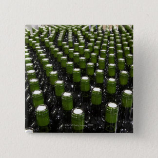 Glass wine bottles in a wine bottling factory. button