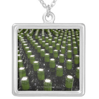 Glass wine bottles in a wine bottling factory. silver plated necklace