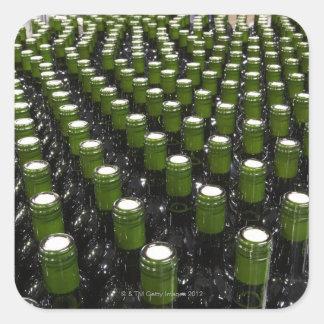 Glass wine bottles in a wine bottling factory. square sticker