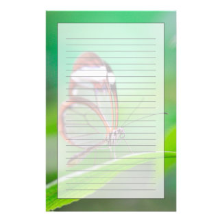 Glass wing butterfly relaxing on fresh green stationery